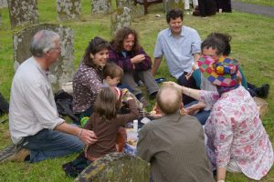 Musicians and members of the audience enjoying a drink and a nibble amongst the gravestones outside Dore Abbey, venue for Concerts for Craswall's summer concerts.