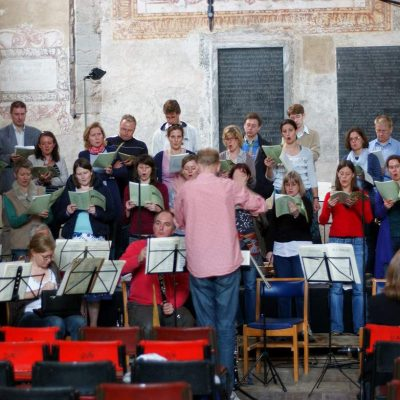 A photograph of The Elysian Singers and conductor Sam Laughton rehearsing in Dore Abbey